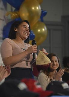 Senior Yasmary Rondon prepared to don a Boston College hat after revealing her college choice. A board at Cristo Rey shows the logos of the colleges the graduates will attend.